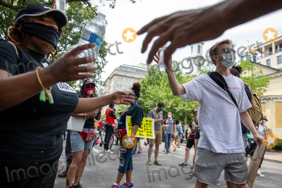 Photo - Volunteers pass out free water near the White House during a march against police brutality and racism in Washington DC on Saturday June 6 2020Credit Amanda Andrade-Rhoades  CNPAdMedia