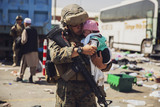 Afghanistan Evacuation Photo - A United States Marine with the 24th Marine Expeditionary Unit (MEU) carries a baby as the familiy processes through the Evacuation Control Center (ECC) during an evacuation at Hamid Karzai International Airport Kabul Afghanistan August 28 2021 US service members are assisting the Department of State with a non-combatant evacuation operation (NEO) in Afghanistan Mandatory Credit Victor Mancilla - US Marine Corps via CNPAdMedia