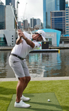 Adam Scott Photo - VICTORIA MELBOURNE AUSTRALIA - DEC 9 Adam Scott hits a golf ball across the Yarra River during the opening of the Presidents Cup at the Fan Experience at the Crown Riverwalk on December 9 2019 in Victoria Melbourne Australia