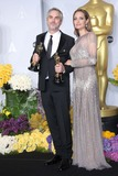 Alfonso Cuaron Photo -  Alfonso Cuaron Angelina Jolie Pose in the Press Room During the Oscars at Loews Hollywood Hotel on March 2nd 2014 Hollywood Californiausa PhototloweGlobephotos